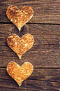 Toast bread in shape of hearts on vintage wooden table Royalty Free Stock Images