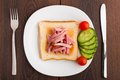 Toast with ham and vegetables on a white plate Royalty Free Stock Image