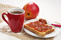 Toast with jam and tea cup of on white table Stock Images