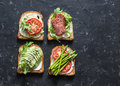 Toast sandwiches with avocado, salami, asparagus, tomatoes and soft cheese on dark background, top view. Tasty breakfast, snack or Royalty Free Stock Photo