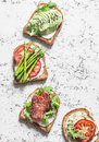 Toast sandwiches with avocado, salami, asparagus, tomatoes and soft cheese on light background, top view. Tasty breakfast, snack o