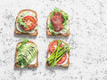 Toast sandwiches with avocado, salami, asparagus, tomatoes and soft cheese on light background, top view. Tasty breakfast, snack o Royalty Free Stock Photo