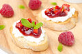 Toasted baguette with cream cheese raspberry jam and mint on a wooden board close up Stock Image