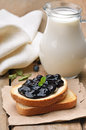 Toasted bread with blueberry jam and milk in glass jug on wooden table Stock Images