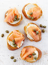 Toasted bread with cream cheese and salmon fillet smoked on wooden table top view Stock Photo