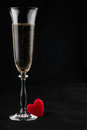 Toasting with champagne and symbolic heart on a black background Stock Image