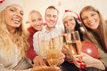 Toasting for christmas or new year happy friends celebrating with glass of champagne and Royalty Free Stock Photos