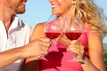 Toasting glasses couple drinking red wine drinks or rose closeup of hands and mouth Royalty Free Stock Photos