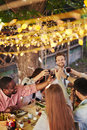 Toasting by table happy friends with red wine at thanksgiving party Stock Image