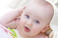 Toddler baby looking aside smiling with teether on white towel Royalty Free Stock Photography