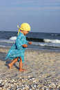 Toddler on the beach walking dressed with a blue dress and yellow bandana looking for seashells Royalty Free Stock Images