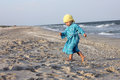 Toddler on the beach walking dressed with a blue dress and yellow bandana looking for seashells Royalty Free Stock Photo