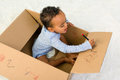 Toddler in a box mixed race little boy sitting cardboard playing with crayons Stock Photo