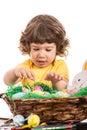 Toddler boy arrange easter eggs in basket a against white background Stock Images