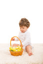 Toddler boy arrange easter eggs in a basket and sitting on fur carpet Stock Photo