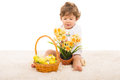 Toddler boy arrange narcissus in pot with easter basket a and sitting on carpet Royalty Free Stock Photo