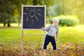 Toddler boy drawing standing by a blackboard Royalty Free Stock Photo
