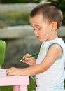 Toddler boy draws a pencil outdoor Stock Photos