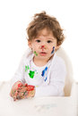 Toddler boy with messy face and hands sitting in a high chiar Stock Image