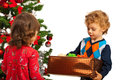 Toddler boy offering gift to his little sister and standing near christmas tree Stock Photos
