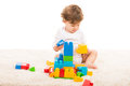 Toddler boy playing on carpet with building blocks against white background Stock Photography
