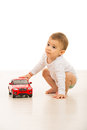 Toddler boy playing with red car and looking away Royalty Free Stock Photos