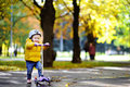 Toddler boy in safety helmet learning to ride scooter Royalty Free Stock Photo
