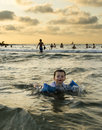 Toddler boy swimming in the ocean at sunset Royalty Free Stock Images