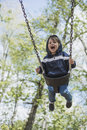Toddler boy swinging in the early spring a young enjoying swing springtime Stock Photography