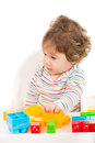 Toddler boy with toys looking away building blocks and thinking Royalty Free Stock Images