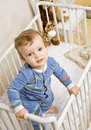 Toddler boy trying to climb out of crib Royalty Free Stock Photography