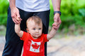 Toddler in canada shirt flag walking assisted by his father room for copy space Royalty Free Stock Image