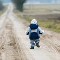 Toddler child walking by rural sandy road Royalty Free Stock Photo
