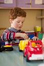 Toddler in classroom playing with toys a young boy on the table a Stock Photos