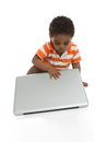 Toddler closing laptop sitting on floor isolated on white background Stock Photo