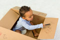 Toddler drawing mixed race little boy sitting in a cardboard box playing with crayons Stock Images