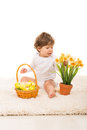 Toddler with easter eggs and narcissus boy basket arrange in a pot sitting on carpet Stock Photo