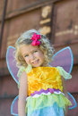 Toddler in fairy halloween costume a smiling little girl with blue eyes and blond hair is dressed a colorful yellow and blue with Stock Image