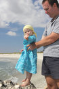 Toddler with father on the beach and Stock Photos