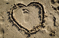 Toddler footprint and heart in sand single right at the beach surrounded by a drawn the brown Royalty Free Stock Image