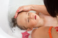 A toddler getting a hairwash by he s mother hair wash in the bath tub is relaxed with eyes closed Stock Photos
