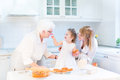 Toddler girl baking apple pie with her grandmothers Royalty Free Stock Photo