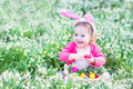 Toddler girl in bunny ears with eggs in spring flowers
