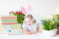 Toddler girl in bunny ears playing with easter pre happy laughing curly hair wearing a blue dress and presents eggs and colorful Royalty Free Stock Photos