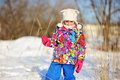 Toddler girl in colorful snowsuit plays in snow Stock Image