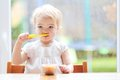 Toddler girl eating fruit puree cute little blonde delicious sitting in the kitchen in a high feeding chair next to a big window Stock Images