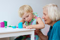 Toddler girl with grandmother creating from plasticine happy little child adorable preschooler using dough colorful modeling Royalty Free Stock Images