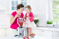Toddler girl and her mother making fresh strawberry happy laughing beautiful young other fruit juice for breakfast together in Royalty Free Stock Image