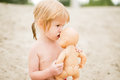 Toddler girl kissing baby doll at the beach on hot summer day playing sand Royalty Free Stock Photo