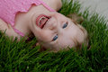 Toddler girl laughing joyously while laying in grass Royalty Free Stock Photo